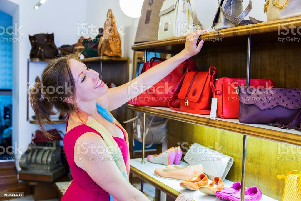 Beautiful young woman buing purse in fancy shop,smiling stock photo
