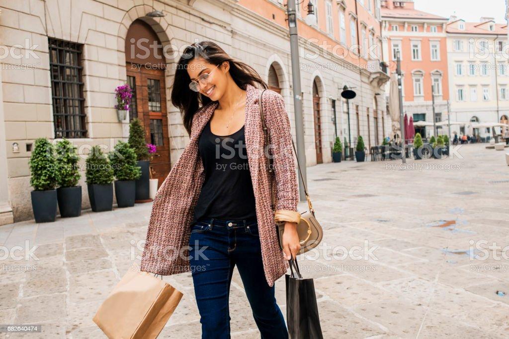 beautiful young woman carrying shopping bags stock photo