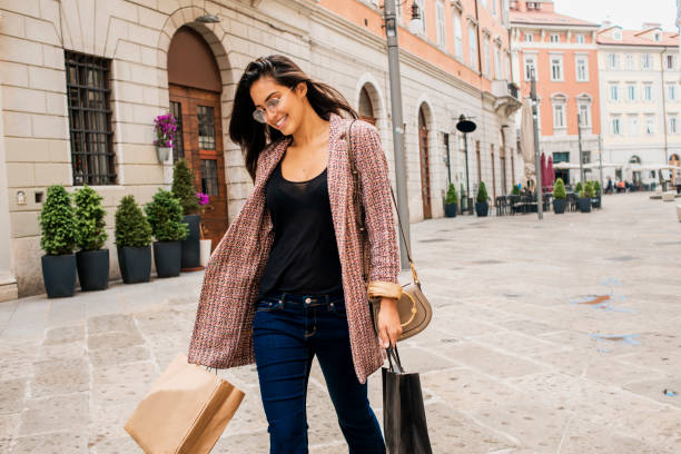 schöne junge frau mit einkaufstaschen - damenjacken stock-fotos und bilder