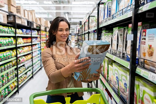 Beautiful young woman choosing a cereal from shelf shopping for groceries at the supermarket smiling **DESIGN ON CEREAL BOX WAS MADE FROM SCRATCH BY US**