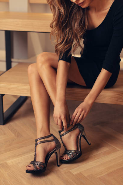 Beautiful young woman choosing and buying shoes in boutique stock photo