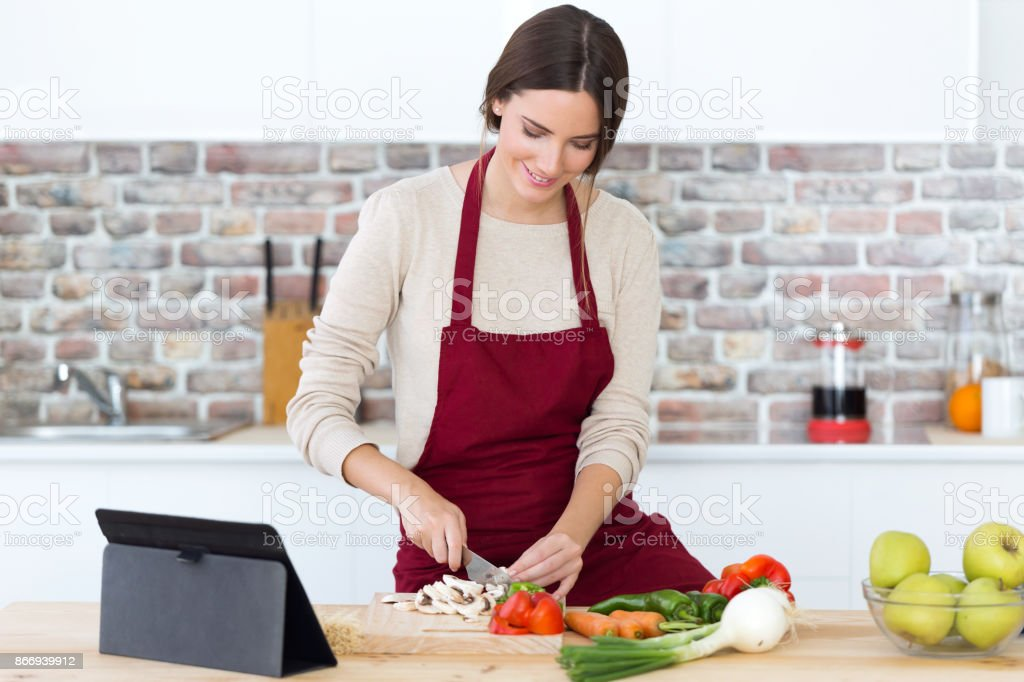 Beautiful young woman cooking and using digital tablet in the kitchen. stock photo