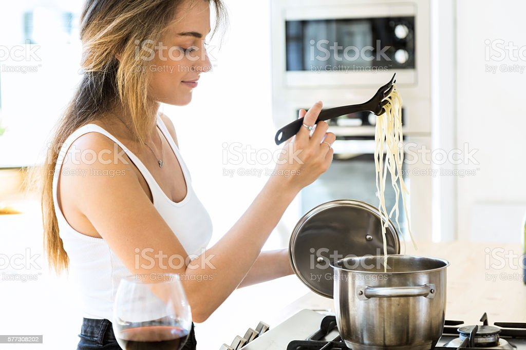 Beautiful young woman cooking spaghetti at home. stock photo