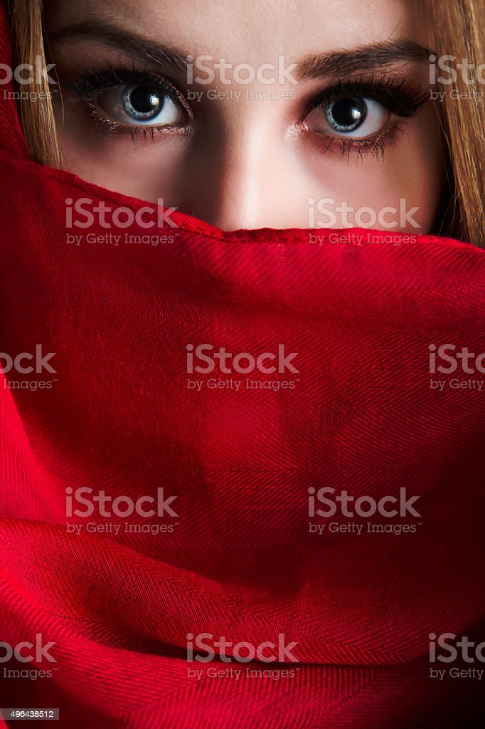 Beautiful young woman covering face with red headscarf stock photo