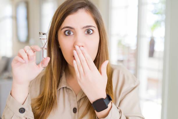 아름다운 젊은 여자 컬링 속눈썹 속눈썹 커버 입을 손으로 실수, 두려움의 표정, 침묵, 비밀 개념에 의해 충격 - 속눈썹 컬러 뉴스 사진 이미지