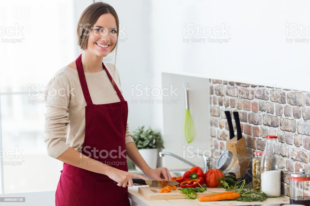Beautiful young woman cutting fresh vegetables in the kitchen. stock photo