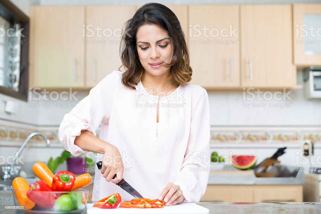 Beautiful Young woman cutting vegetables stock photo