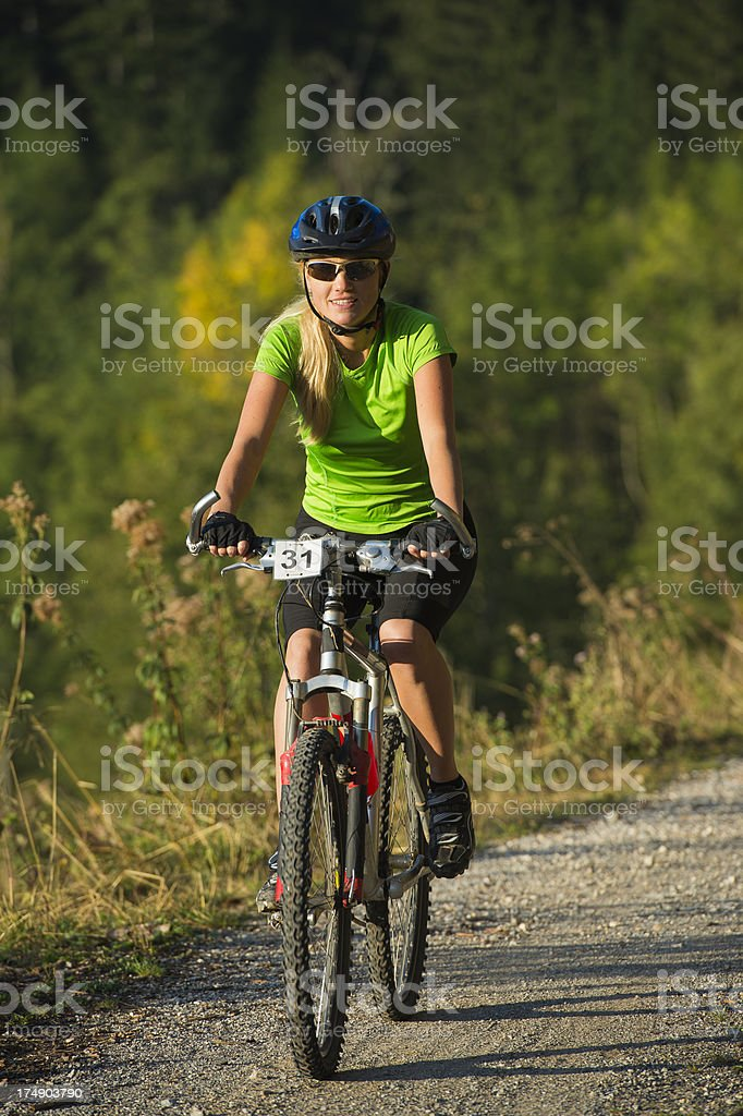 Beautiful young woman cycling on the country road royalty-free stock photo