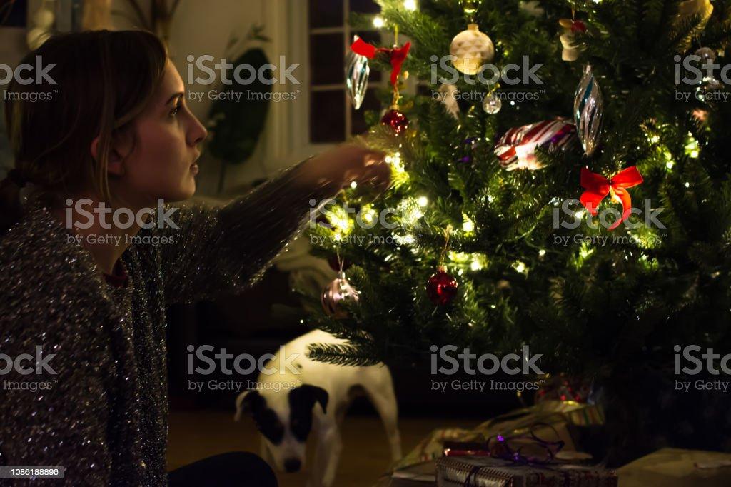 Beautiful young woman decorating Christnas tree next to illuminated Christmas  tree stock photo