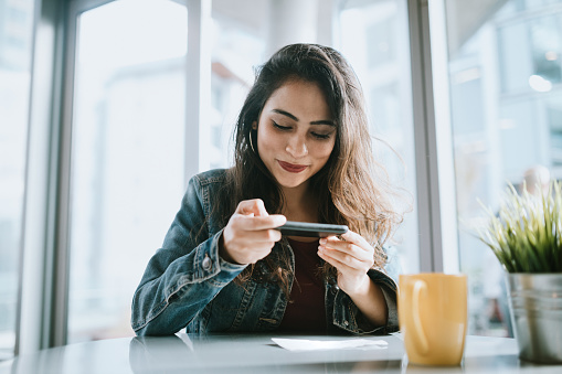Beautiful Young Woman Depositing Check With Smartphone