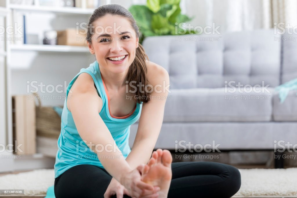 A beautiful young woman smiles for the camera as she stretches her...