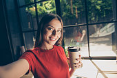 Beautiful young woman doing selfie on the front camera of her smartphone and holding a paper cup with a drink