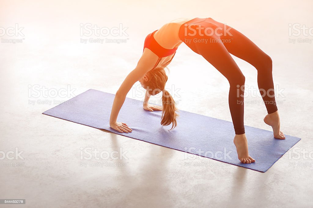Beautiful young woman doing yoga exercise Bridge Pose stock photo