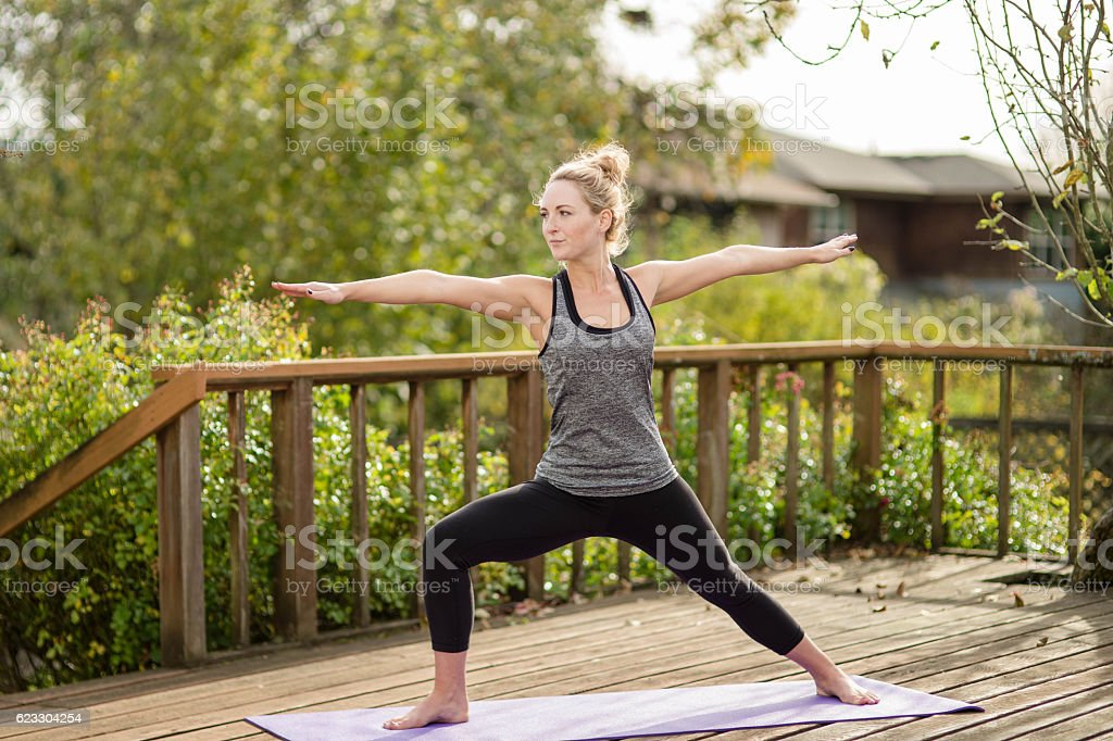 Beautiful young woman doing yoga on back porch stock photo