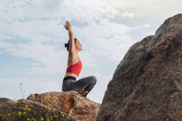 schöne junge frau, die beim yoga auf felsen sitzend - immunsystem stärken stock-fotos und bilder