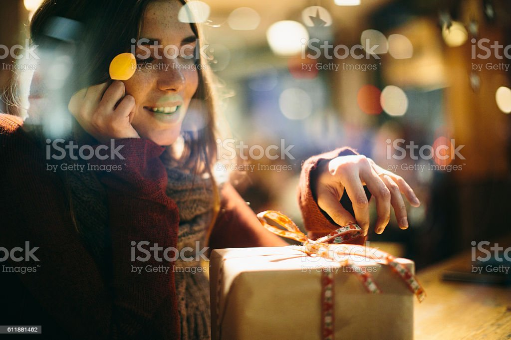 Beautiful young woman dreaming with christmas present stock photo