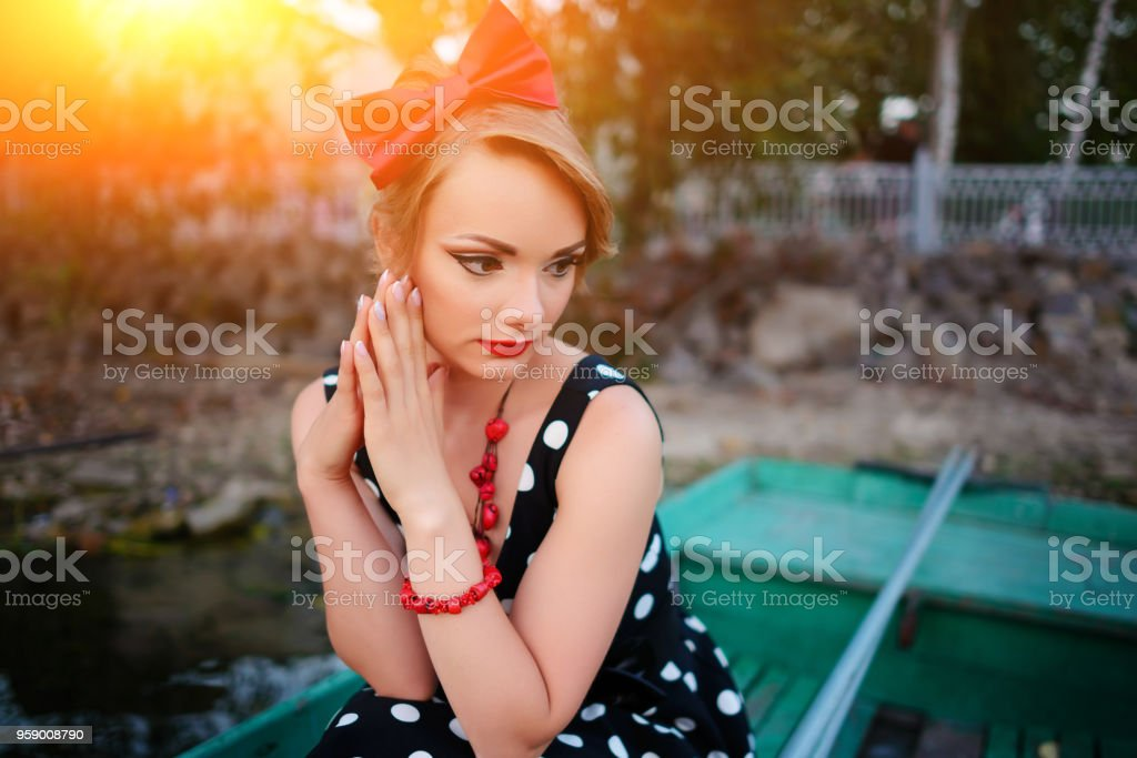 Beautiful young woman dressed dressed in a boat on a lake shore stock photo