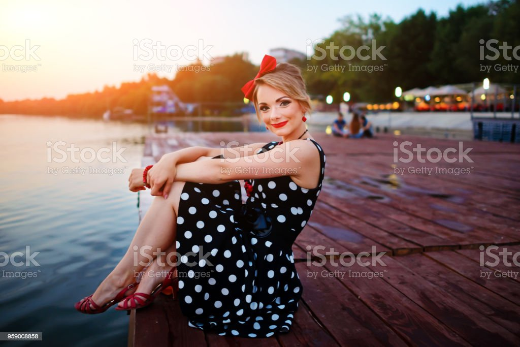 A beautiful young woman dressed sitting on the pier stock photo