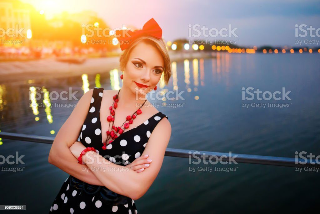 A beautiful young woman dressed stand on the pier in the evening stock photo