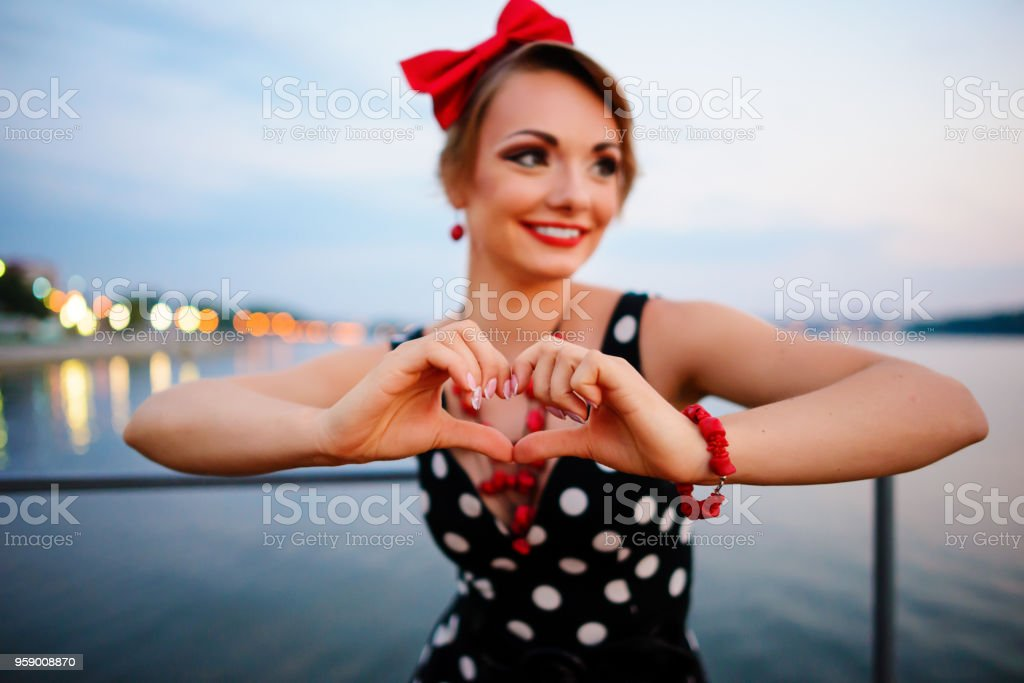 A beautiful young woman dressed stand on the pier in the evening, shows with his own hands the heart stock photo