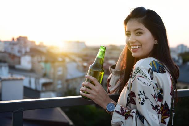 Schöne junge Frau, die bei Sonnenuntergang Bier auf dem Balkon trinkt – Foto