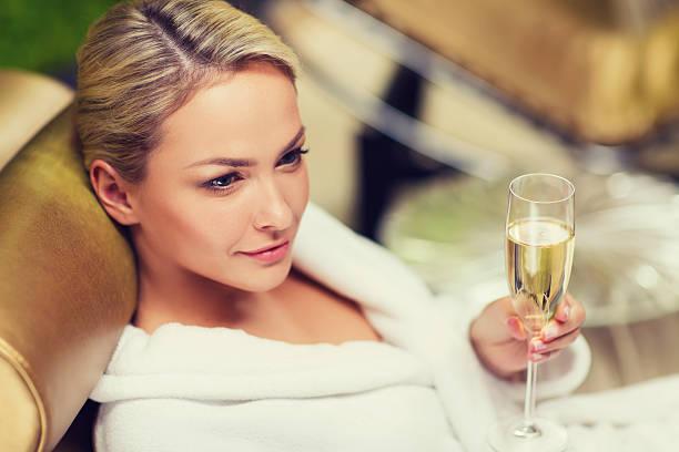 bellissima giovane donna bere champagne alla spa - accappatoio foto e immagini stock