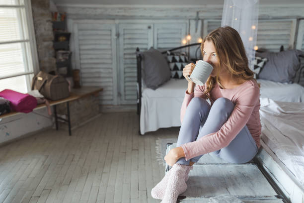 Beautiful young woman drinking coffee at home