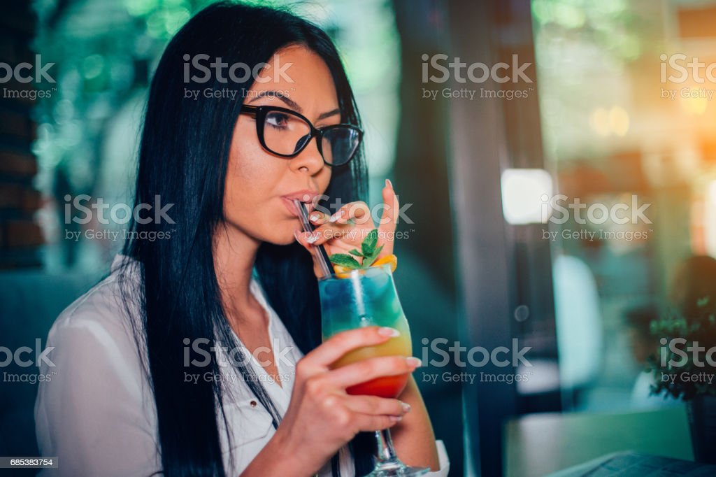 Beautiful young woman drinking colorful cocktail at the bar foto de stock royalty-free