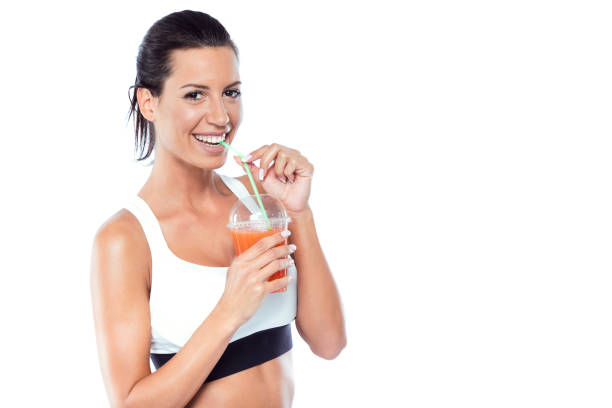 Beautiful young woman drinking detox juice over white background. stock photo