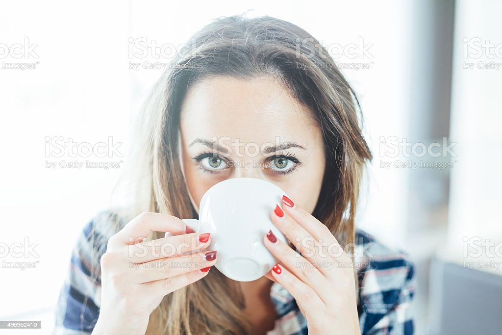 Beautiful young woman drinking from a cup stock photo