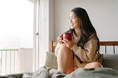 A beautiful young woman is drinking a cup of hot drink in her bed and looking out of the widow in the morning.