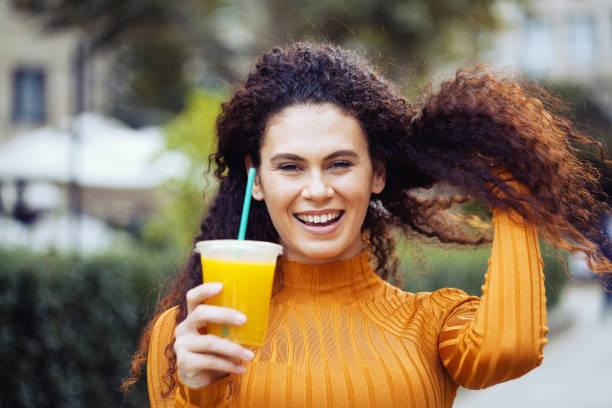 Beautiful young woman drinking orange juice stock photo