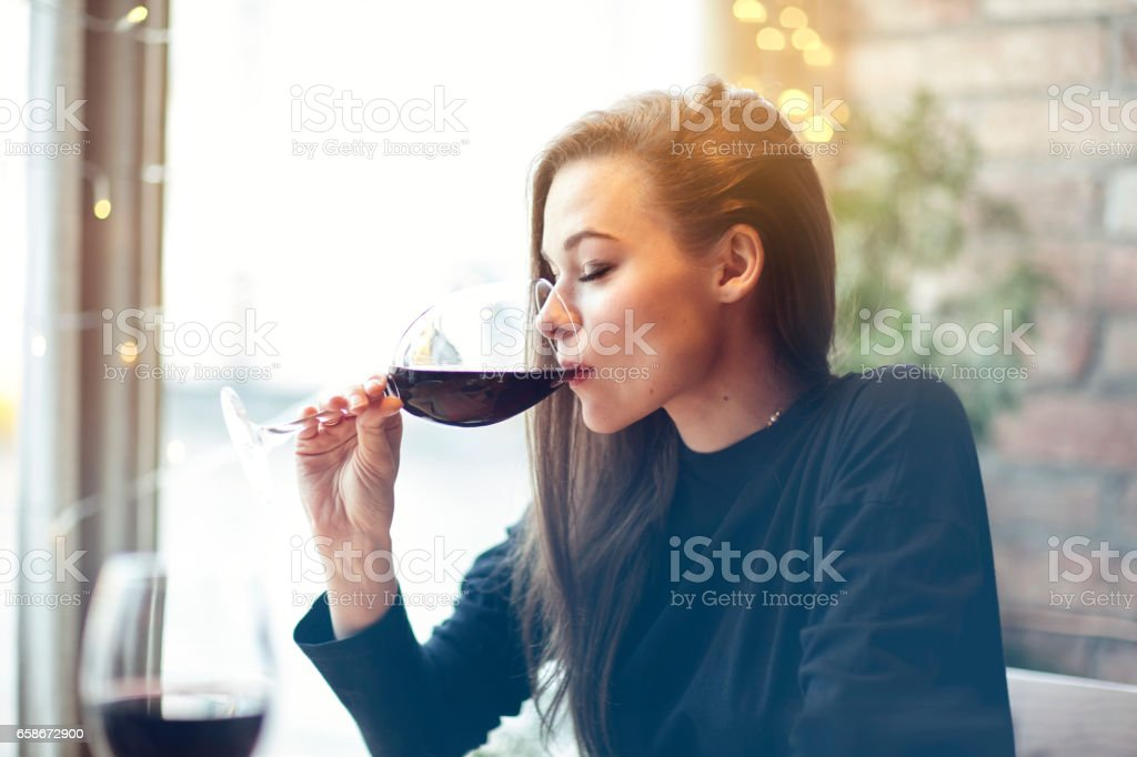 Beautiful young woman drinking red wine with friends in cafe, portrait with wine glass near window. Vocation holidays evening concept - foto de stock