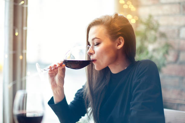 Beautiful young woman drinking red wine with friends in cafe, portrait with wine glass near window. Vocation holidays evening concept - Photo