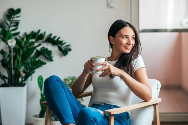 hermosa joven tomando té en su casa. mirando lejos. - café bebida fotografías e imágenes de stock