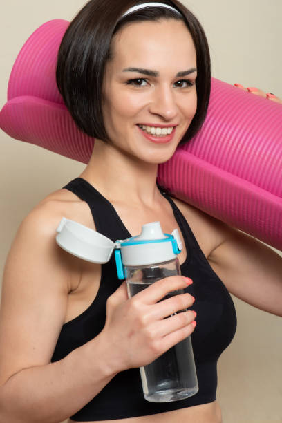 Beautiful young woman drinking water after a workout at home stock photo