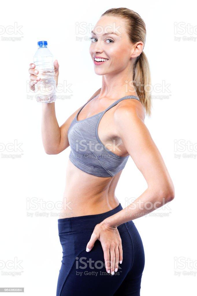 Mulher jovem e bonita água potável depois de fazer exercício sobre fundo branco. - Foto de stock de Adulto royalty-free