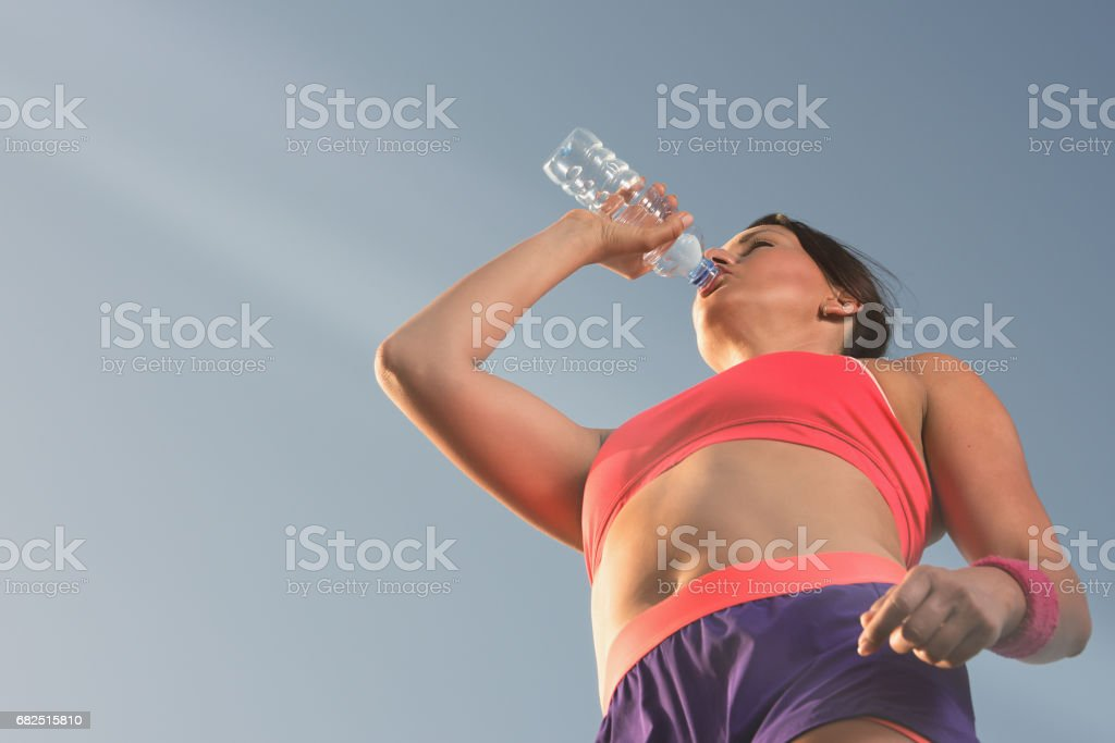 Beautiful young woman drinking water after training foto stock royalty-free