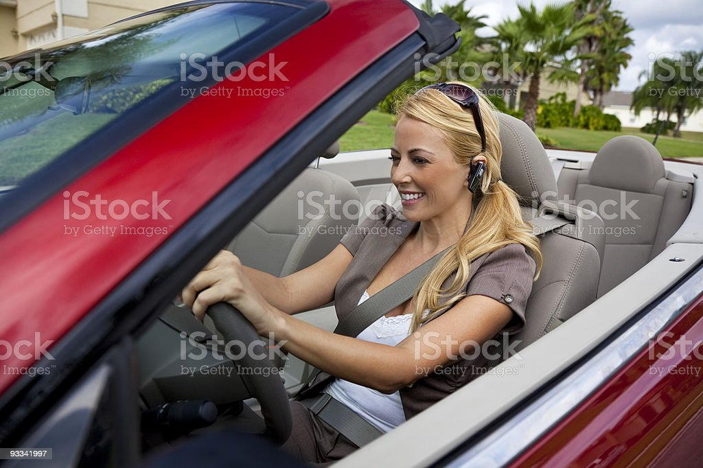 Beautiful Young Woman Driving Convertible Car Talking on Bluetooth Headset stock photo