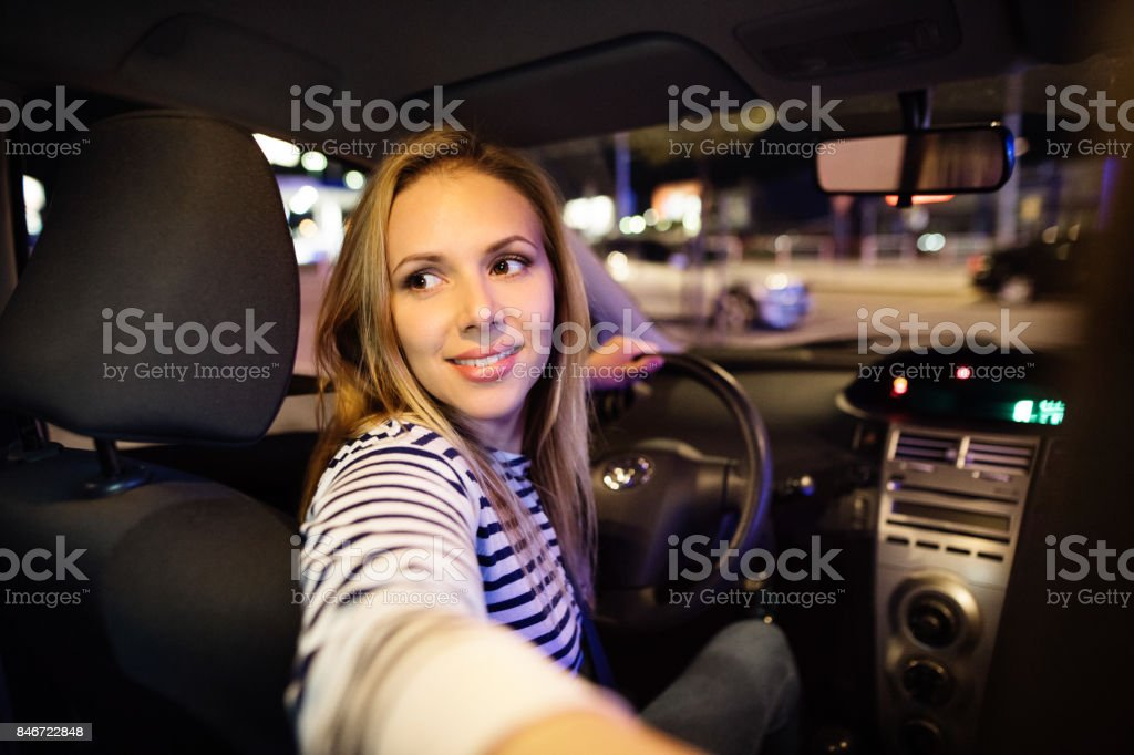 Beautiful young woman driving her car at night. stock photo
