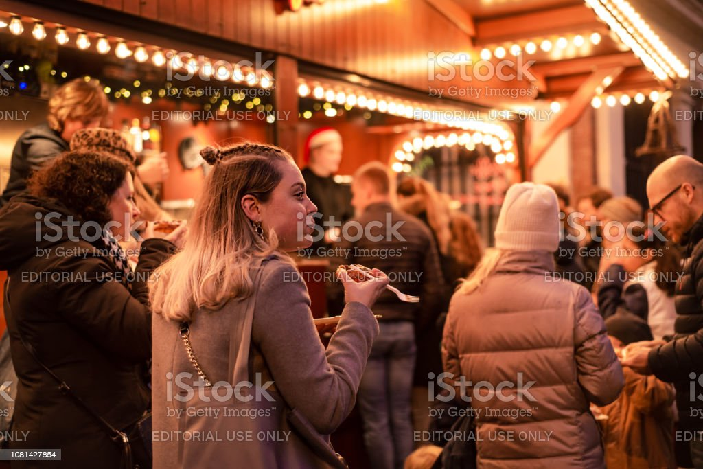Beautiful young woman eating a stroopwafel (syrup waffle) at a Dutch, Christmas street market stock photo