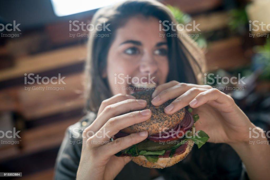 Mulher jovem e bonita comendo um pãozinho de vegetariano, enquanto olhando para longe - foto de acervo