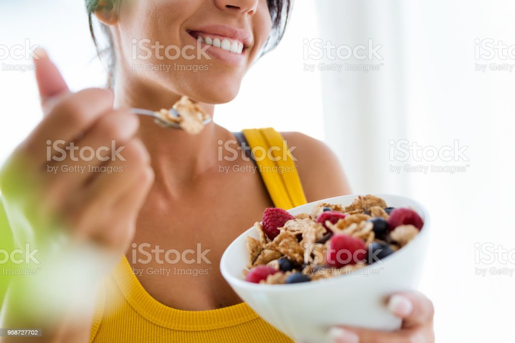 Beautiful young woman eating cereals and fruits at home. stock photo