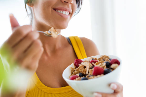 beautiful young woman eating cereals and fruits at home. - mangiare sano foto e immagini stock