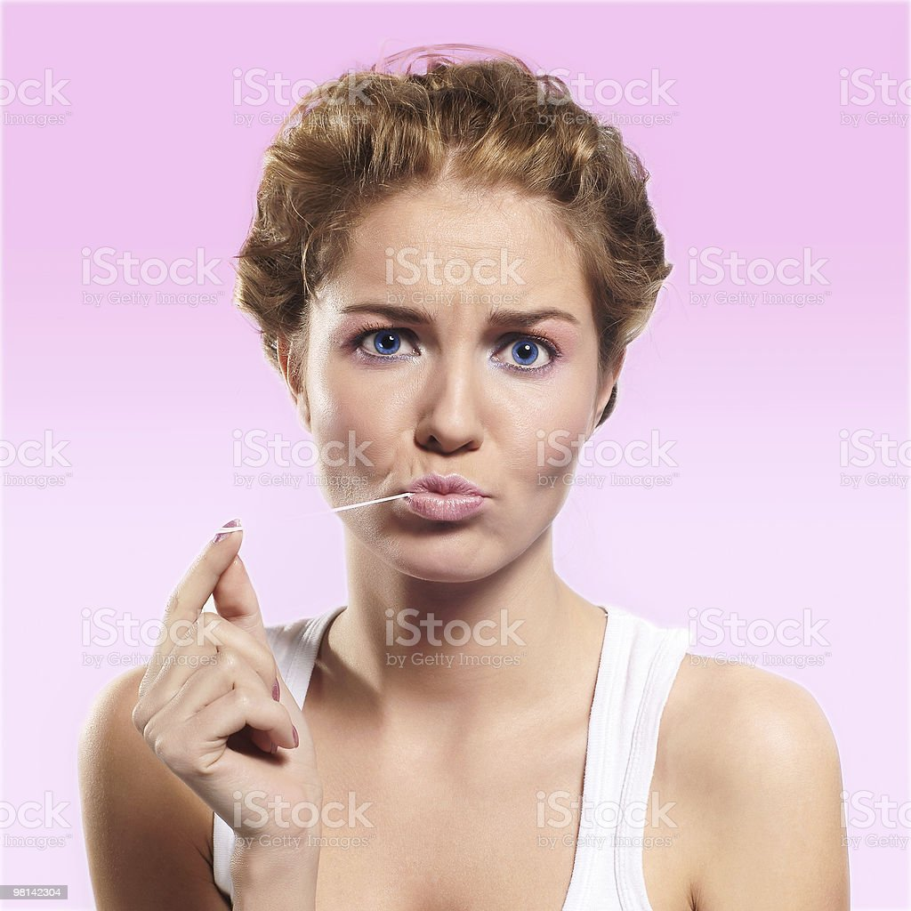 Beautiful young woman eating chewing gum, smiling royalty-free stock photo