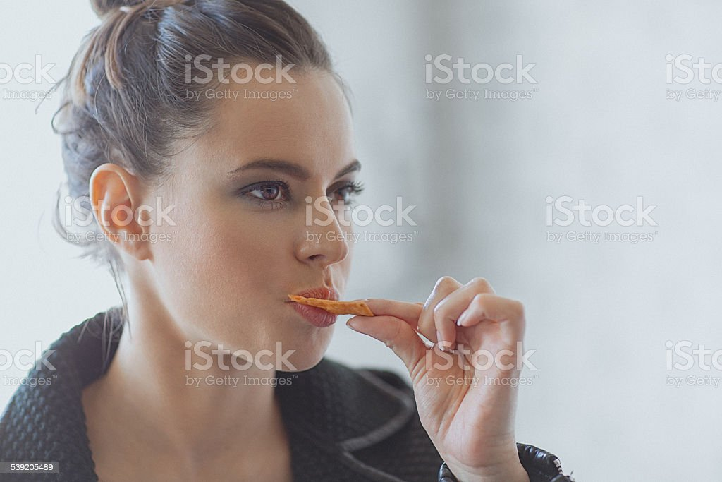 Beautiful young woman eating muesli bar snack stock photo