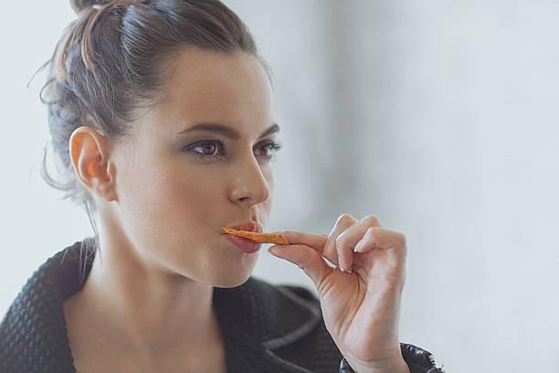 beautiful young woman eating muesli bar snack - 克力架 個照片及圖片檔