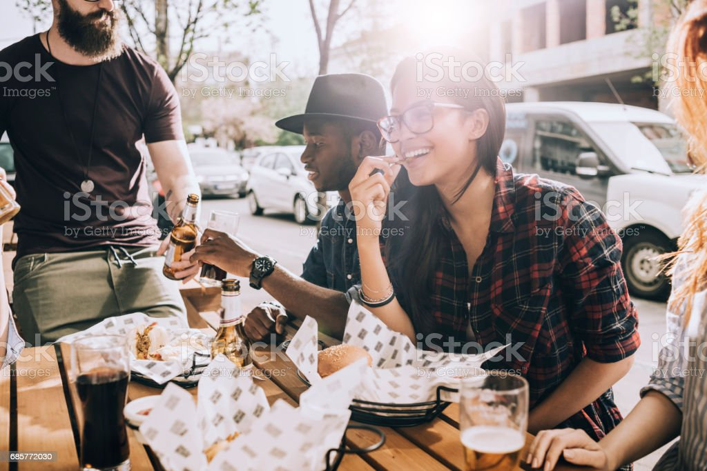 beautiful young woman eating outdoors with her friends - foto stock