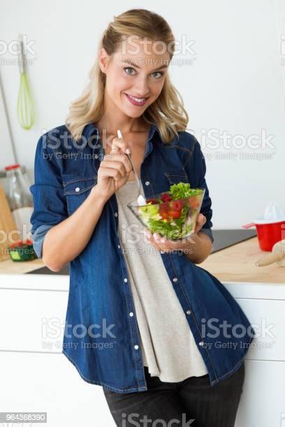 Foto de Mulher Jovem E Bonita Em Casa A Comer Salada e mais fotos de stock de Adulto