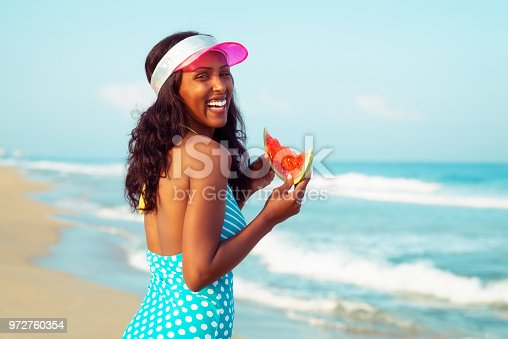 Happy woman eating a slice of watermelon, looking at camera over a shoulder, laughing. The woman wearing blue retro vintage swimwear with white polka dots and pink sun visor. Summer holiday vacation on the sea beach. Purple film filter applied.